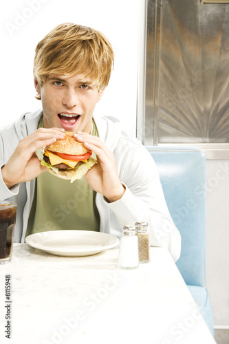 Teenage boy eating a large hamburger in a diner