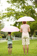 rear view woman and girl with umbrellas up