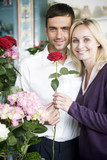 Couple choosing flowers in a florist's shop, red roses