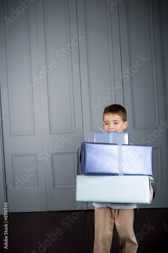 little boy carrying presents