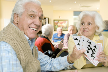 Two residents in a retirement home playing cards