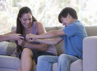 A brother and sister fighting over the remote control