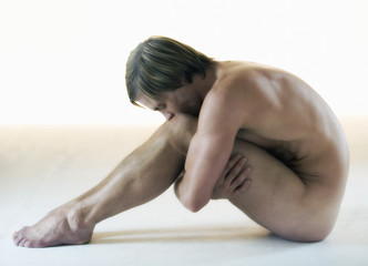 A male nude, sitting