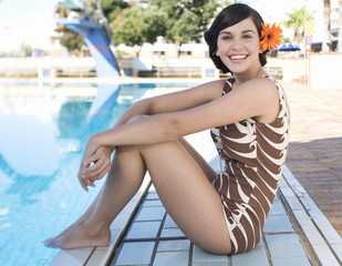 A young woman sitting by a swimming pool