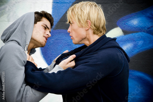 Two men fighting in front of a graffiti covered wall