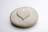 a stone with an engraved heart on a metal surface poster