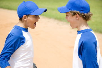 two boys in baseball gear shouting at each other
