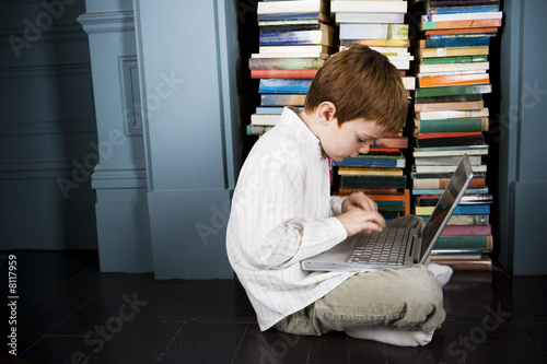 boy with laptop sitting on the floor