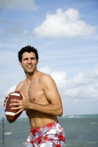 A young man with a ball on the beach