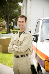 Removal man standing beside their van with packing boxes