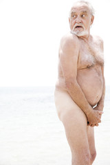 Naked senior man covering himself up with his hands