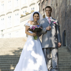 A bride and groom walking down steps
