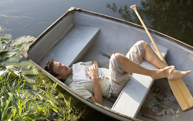 Young man asleep in a boat