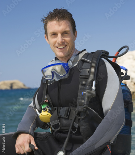A male scuba diver sitting on a boat