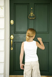 Little girl knocking at the front door of a house