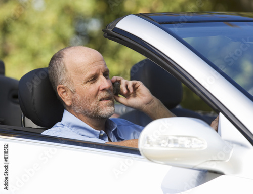 A senior man driving a car whilst on a cell phone