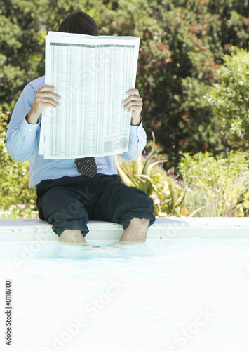 A businessman sitting by a swimming pool reading the paper