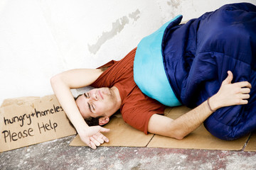 Homeless young man laying in the street