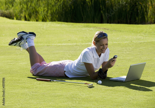 Woman using a laptop and mobile phone whilst on the golf course