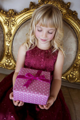 Portrait of a little girl holding birthday presents