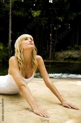 Beauty portrait of a woman doing yoga in a tropical setting.