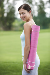 A young woman with a yoga mat