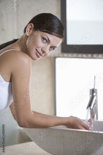 A woman washing at a sink