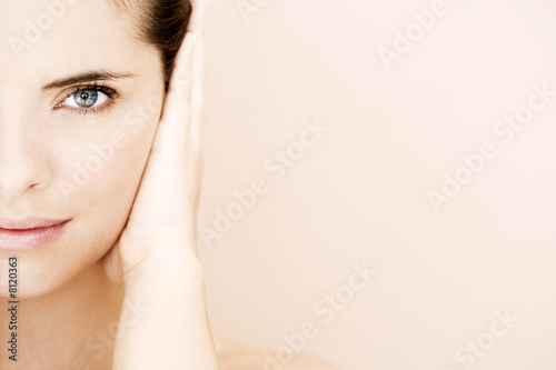 Cropped portrait of young woman's face with hand over her ear, hear no evil