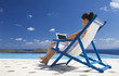A woman sitting on a deck chair using a laptop