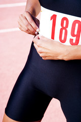 Close in crop of a female athlete attaching her competitors number