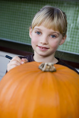 Little girl making a pumpkin lantern.