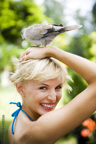 Beauty portrait of a woman in a tropical setting with a dove on her head.