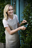Woman florist or gardener pruning a bay tree outside her shop