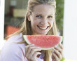 A woman eating a slice of watermelon