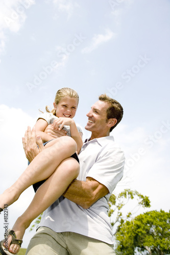 father carrying daughter in his arms
