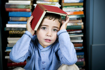 little boy with book on his head