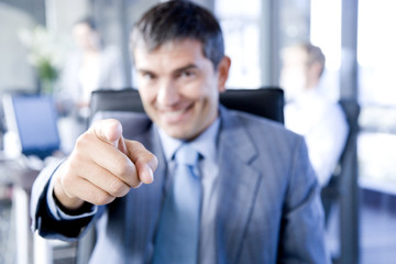 Smiling businessman pointing towards camera