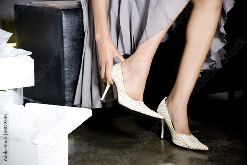 Woman trying on high-heeled shoes in a shoe shop