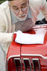A senior man polishing a sports car