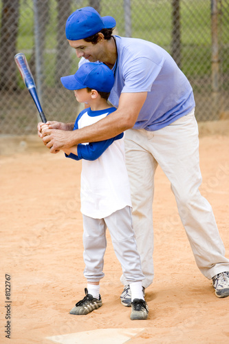 Young boy being taught how to swing a baseball bat