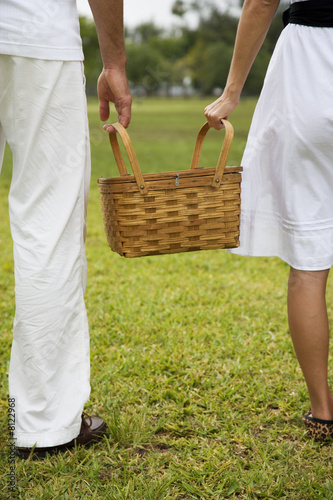cropped image couple walking with picnic basket