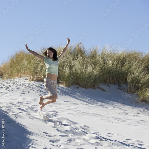 Young woman jumping in sand dunes