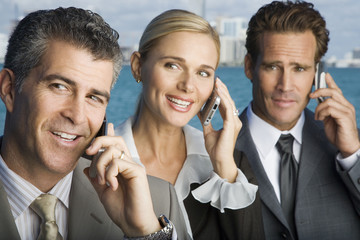 Three business colleagues talking on mobile phones