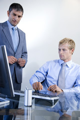 Two businessmen looking at a computer in a modern office