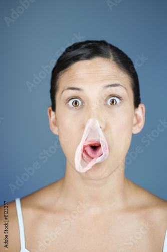 A young woman chewing bubble gum