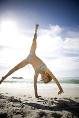 A young girl cartwheeling on the beach