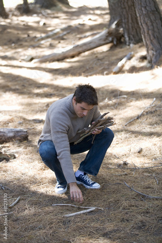 A young man collecting fire wood