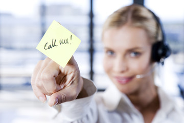Woman with a call centre headset and a sticky notelet saying Call Me