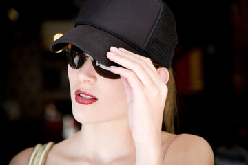 Woman in a baseball cap and sunglasses outdoors