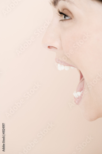 Profile of young woman with mouth open wide, shouting
